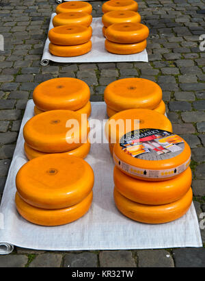 Gouda cheese wheels piled up on the cheese market, Gouda, Netherlands - Stock Photo