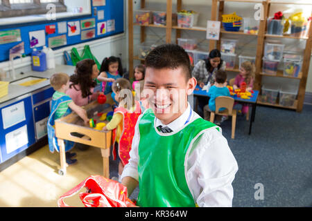 Teacher in a classroom. He is holding some aprons and smiling at the camera. The children are playing in the background - Stock Photo