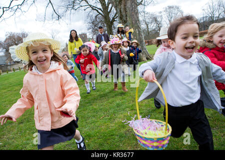 Nursery children running across a field during their outdoor Easter egg hunt, they are wearing handmade hats and - Stock Photo
