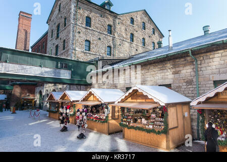 Small temporary stalls with vendors selling Christmas goods in the revitalized and historic Distillery district - Stock Photo