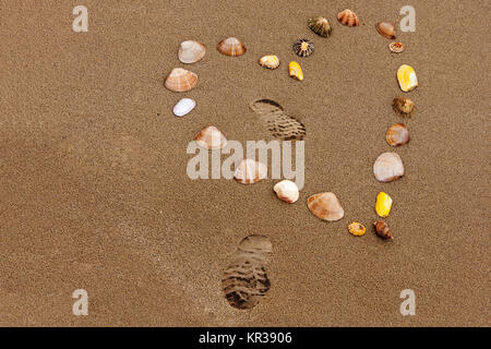 Heart shape in the beach sand made from shells - Stock Photo