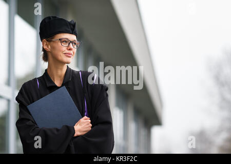 Pretty, young woman celebrating joyfully her graduation - cheking her diploma, happy/impressed with the title she - Stock Photo