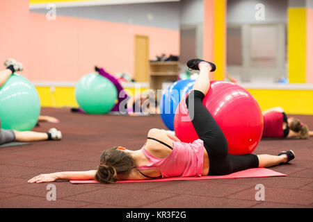 Group people in a pilates class at the gym - young woman with gymball at fitness training (shallow DOF, color toned - Stock Photo