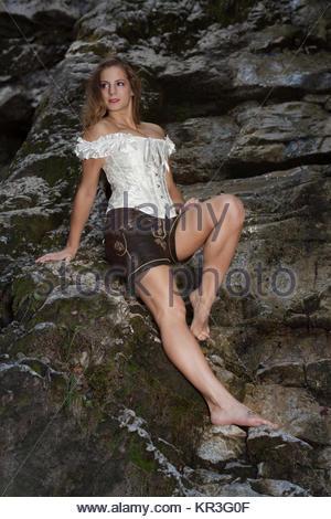Junge blonde Frau auf Felsenuntergrund -  verführerisch, erotisch und verträumt zugleich - Stock Photo