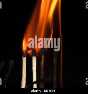 Burning matches on black - Stock Photo