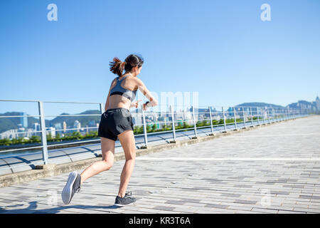 Woman running in a city and using smart watch for record - Stock Photo