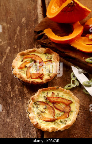 Appetizing small butternut, leek and custard quiches with a crispy pastry crust on a rustic wooden kitchen table with fresh ingredients, high angle view