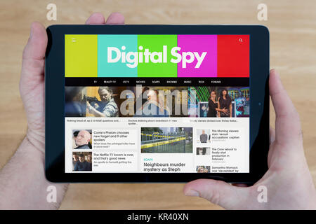 A man looks at the Digital Spy website on his iPad tablet device, shot against a wooden table top background (Editorial - Stock Photo