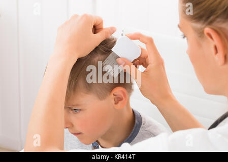 Doctor Doing Treatment On Boy's Hair - Stock Photo