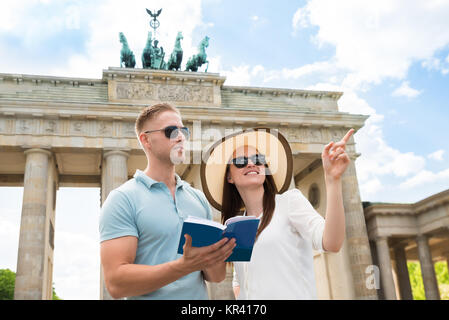 Young Couple Reading Tourist Guide - Stock Photo
