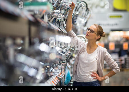 Pretty young woman choosing a bathroom/kitchen tap in a home furnishings retail store - Stock Photo