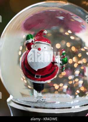 Close up of a skating Santa in a snow globe with golden points of light in the background. - Stock Photo