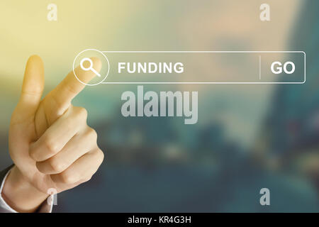 business hand clicking funding button on search toolbar - Stock Photo