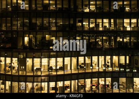 yellow light windows of an office building at night in Boston late night at work glass curtain wall office building - Stock Photo