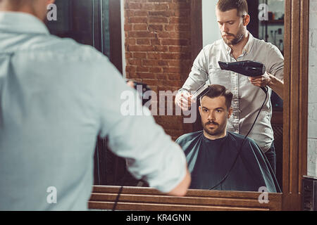 Young handsome barber making haircut of attractive man in barbershop - Stock Photo