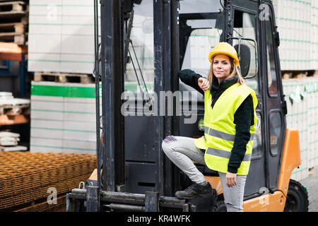 Woman forklift truck driver in an industrial area. - Stock Photo
