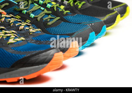 Three pairs of colourful exercise trainers / running shoes lined up in a row on a white background with copy space. - Stock Photo