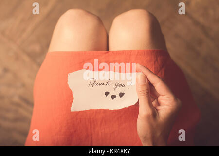 Woman holding a thank you note in her hand - Stock Photo