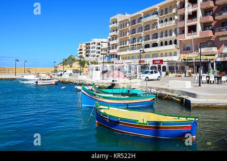 Traditional Maltese Dghajsa fishing boats in the harbour with bars and restaurants to the rear, Marsalforn, Gozo, - Stock Photo