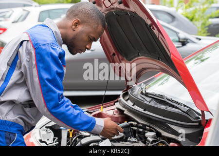 Mechanic Checking Car Battery With Multimeter - Stock Photo