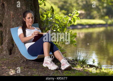 Young pregnant  woman with book sits in the park. - Stock Photo