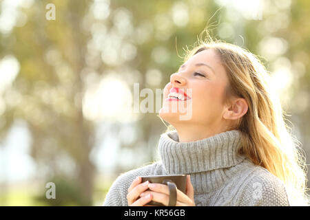 Portrait of a happy lady wearing a grey jersey breathing fresh air holding a cup of coffee in a park in winter - Stock Photo
