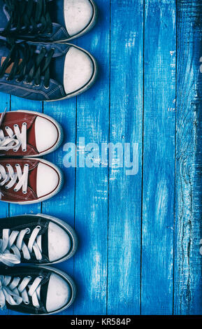 Three pairs of old sneakers on blue worn wooden background - Stock Photo