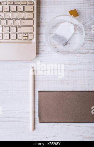 Laptop and notebook and a cup on a wooden table - Stock Photo