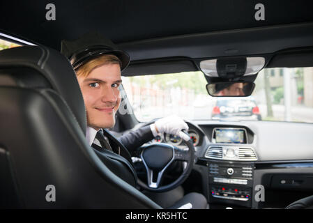 Portrait Of Smiling Young Chauffeur In Car - Stock Photo