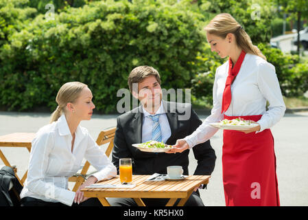 Waitress Serving Food To Businesspeople - Stock Photo