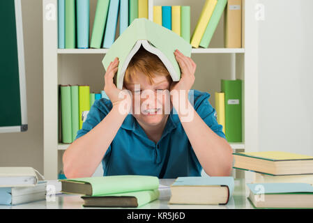 Angry Boy Sitting In Library - Stock Photo