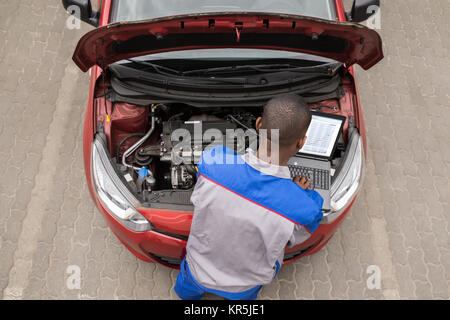 Mechanic With Laptop While Examining Engine - Stock Photo