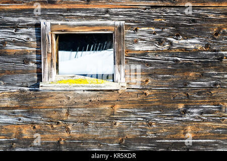 Vintage window of old wooden cabin mirrors winter landscape. Wooden rustic background. - Stock Photo