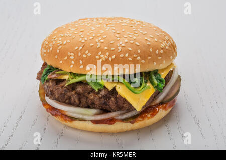 hamburger with meat cutlet, pickle, onion, cheese, spinach and spicy sauce. bun with sesame over white wooden background - Stock Photo
