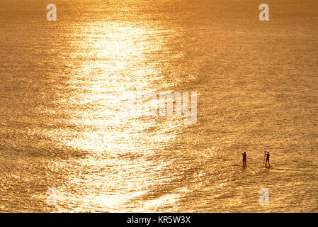 Cuckmere Haven, East Sussex. 18th December 2017. The morning sun illuminating paddle boarders near Cuckmere Haven - Stock Photo