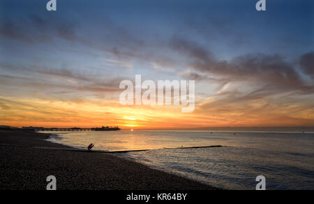 Brighton, UK. 19th Dec, 2017. A runner stops to take a photograph of the beautiful sunrise along Brighton seafront - Stock Photo