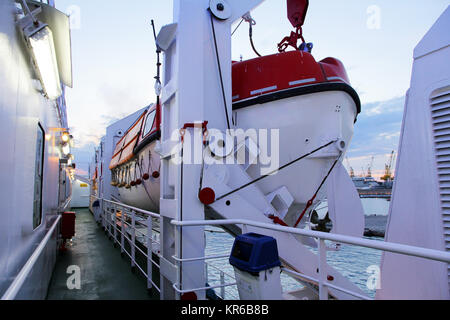 lifeboats on a car ferry in the evening light - Stock Photo