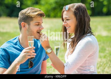 Woman Feeding Grape To Her Boyfriend - Stock Photo