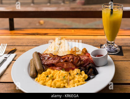 Enjoing a big breakfast with eggs, bacon, tomats, sausages, bread, ketchup, musrooms and a fruit drink in Ao Nang - Stock Photo