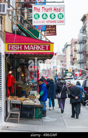 Exterior of a fishmongers with fish on display and owner outside as people walk past, Chinatown, New York, USA - Stock Photo