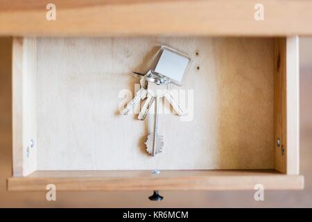 bunch of door keys with keyfob in open drawer - Stock Photo