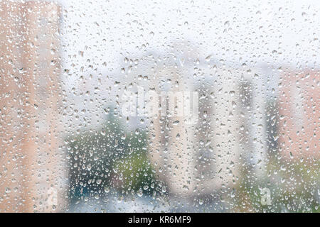 view of raindrops on window glass of urban house - Stock Photo