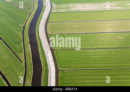 Aerial view of canal and dyke running through reclaimed low-lying agricultural land. - Stock Photo