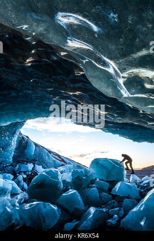 Side view of person climbing up on ice rock at the entrance to a glacial ice cave. - Stock Photo