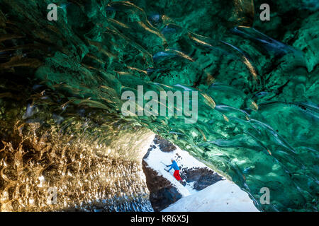 View through glacial ice cave with climber in the background. - Stock Photo