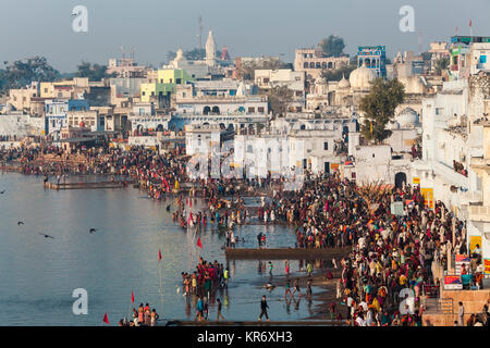 High angle view of cityscape with large group of pilgrims on the shore of a lake. - Stock Photo