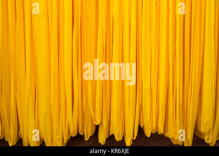 Close up of freshly dyed bright yellow fabric hanging up to dry. - Stock Photo