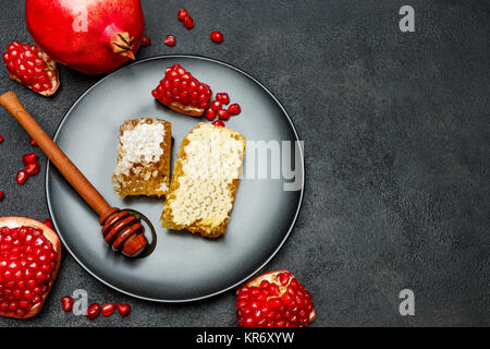 Pomegranate and honeycomb close-up on dark concrete background - Stock Photo