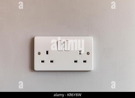 UK domestic 3 pin double plug electrical socket in white plastic on a beige coloured wall - Stock Photo