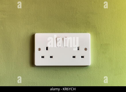 UK domestic 3 pin double plug electrical socket in white plastic on a green coloured wall - Stock Photo